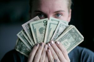 a woman holding dollar bills in front of face